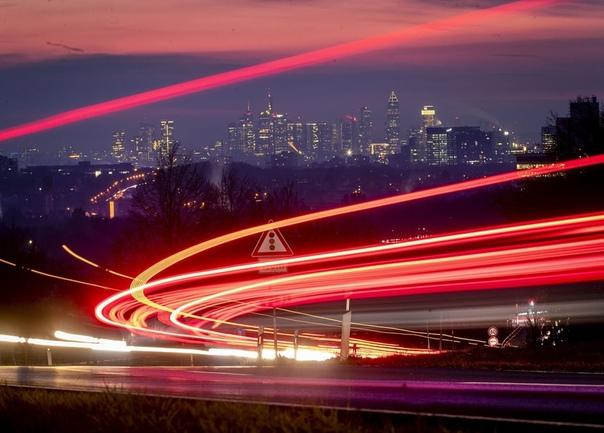 Автомобильная трасса, снятая на длинной выдержке, на фоне Банковского района Франкфурта, Германия