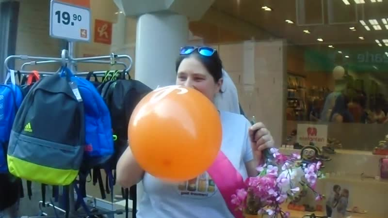 Woman blows to pop an orange balloon outside